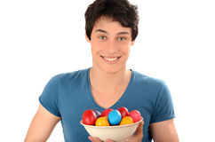 Happy young man holding a basket with Easter eggs. Royalty Free Stock Photos