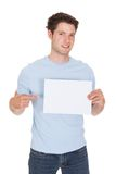 Happy Young Man Holding Blank Placard Royalty Free Stock Photography
