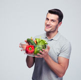 Happy young man holding bowl with vegetables Royalty Free Stock Photo