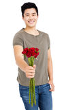 Happy young man holding bunch of red roses Stock Photography