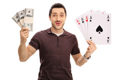 Happy young man holding bundles of money and four aces Stock Photo