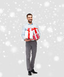 Happy young man holding christmas gifts over snow Stock Image