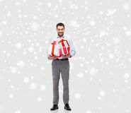 Happy young man holding christmas gifts over snow Stock Photo