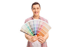 Happy young man holding a color swatch. Isolated on white background stock photo