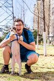Happy young man holding dog outdoors in the urban park in a sunny day. Happy young caucasian man holding dog in hands at sunny day in the park outdoors stock images