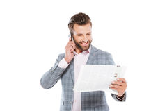 Happy young man holding gazette and talking by mobile phone Royalty Free Stock Images