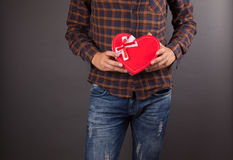 Happy young man holding gift box. Over gray background Royalty Free Stock Photography