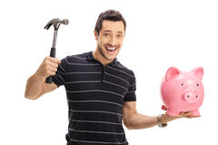 Happy young man holding a hammer and a piggybank. Isolated on white background royalty free stock photo