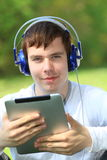 Happy young man holding an ipad Stock Images