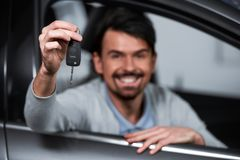 Car sales. Happy young man is holding keys to new car and looking at the camera. Focus on keys stock photo