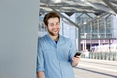 Happy young man holding mobile phone Stock Images
