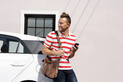 Happy young man holding mobile phone outside Royalty Free Stock Photography