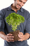 Happy Young Man Holding Plant Stock Photo