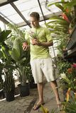 Happy Young Man Holding Potted Plants Stock Photo