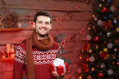 Happy young man holding present in christmas time Stock Photo