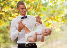 Happy young man holding a smiling baby. Happy young men holding a smiling 7-9 months old baby Royalty Free Stock Photos