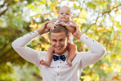 Happy young man holding a smiling baby. Happy young men holding a smiling 7-9 months old baby Stock Images