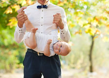 Happy young man holding a smiling baby. Happy young men holding a smiling 7-9 months old baby Royalty Free Stock Photo