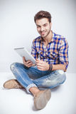 Happy young man holding a tablet pad computer. Happy young fashion man holding a tablet pad computer while relaxing on the floor, looking at the camera Stock Photography