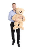 Happy young man holding a teddy bear getting soon a baby. Royalty Free Stock Image