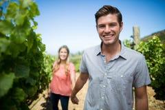 Happy young man holding woman hand at vineyard Royalty Free Stock Photos