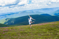 A happy young man holds a woman high in the mountains royalty free stock photography