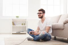Happy young man at home playing video games. Young man playing video games at home. Happy guy in glasses sitting on floor with joystick in hands, copy space Royalty Free Stock Images