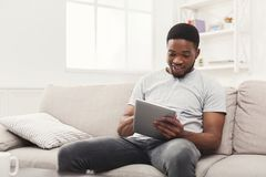 Happy young man at home reading on tablet Royalty Free Stock Image