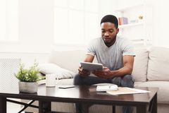 Happy young man at home reading on tablet Royalty Free Stock Photography