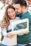 Happy young man hugging his wife or girlfriend. Woman is smiling after opening a gift box royalty free stock image