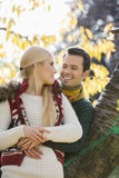 Happy young man hugging woman while leaning on tree trunk during autumn in park Stock Photos