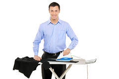 Happy young man ironing his clothes Stock Image