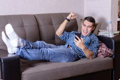 Happy young man in jeans, a plaid shirt and white socks lying on the couch with a smartphone and is happy raising his hand up stock image