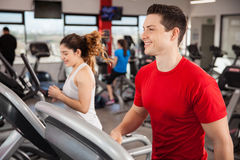 Happy young man jogging at the gym. Good looking young men jogging on a treadmill at the gym and smiling royalty free stock photography
