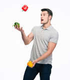 Happy young man juggling pepper Royalty Free Stock Photography