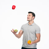 Happy young man juggling pepper Stock Photos
