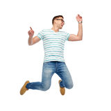 Happy young man jumping in air. Happiness, freedom, motion and people concept - happy young man jumping in air stock photography
