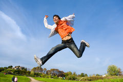 Happy young man - jumping  end flies in blue sky. Stock Photo