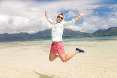 Happy young man jumping of joy on the beach Stock Photography