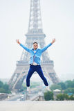 Happy young man jumping near the Eiffel tower in Paris. France Royalty Free Stock Photo
