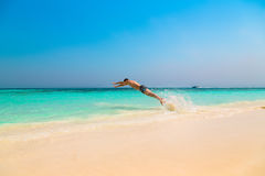 Happy young man jumping into the ocean Royalty Free Stock Images