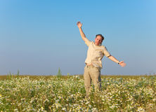 The happy young man jumps in the field of chamomiles Royalty Free Stock Images