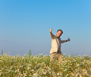 The happy young man jumps in the field of chamomiles Stock Photo