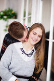 Happy young man kissing his girlfriend in the neck Royalty Free Stock Image