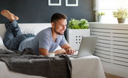 Happy young man with laptop and cup of coffee in bed Stock Photos