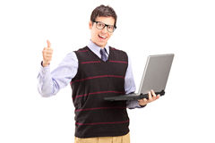 Happy young man with laptop showing thumb up Stock Photos