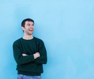 Happy young man laughing against blue background stock photography