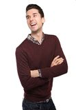 Happy young man laughing with arms crossed Royalty Free Stock Images
