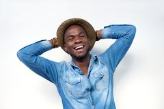 Happy young man laughing with hands behind Stock Images