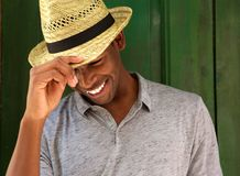 Happy young man laughing with hat and looking down Royalty Free Stock Images